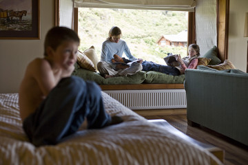 Two teenage relaxing in a room with their younger brother.