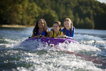 Three giggling girls riding together on an inner tube being pulled along in a river.