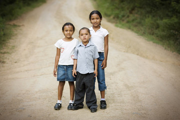View of three children standing on a road.