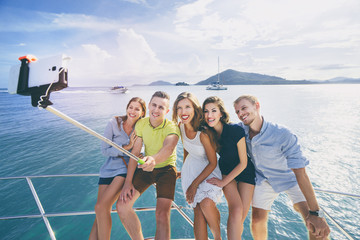 Friendship and vacation. Group of young handsome men and women taking selfie together on the yacht sailing the sea.