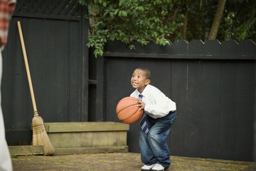 Young boy crouching with a basketball.