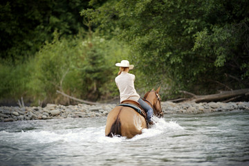 Mid-adult woman riding a horse through a river.