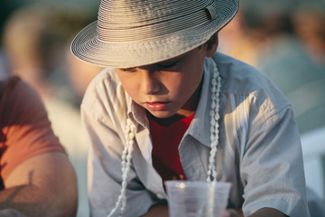 Portrait of boy wearing a shell necklace and a sunhat on holiday.