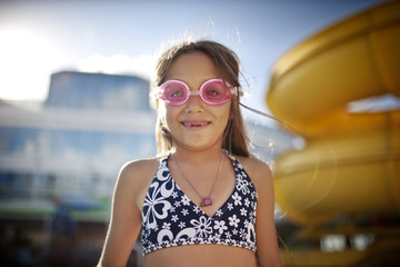 Young girl with missing teeth wearing swimming goggles at a swmming pool.