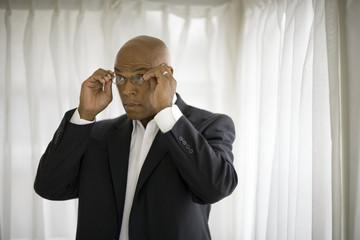 Mid-adult businessman putting on reading glasses.