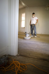 Male builder buffing floorboards inside a room.