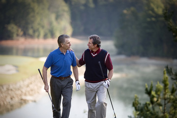 Two mature men enjoying a game together on a golf course.
