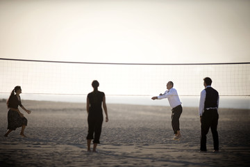 Two couples are playing volleyball on the beach.