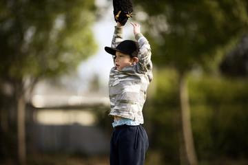 boy tries to catch baseball
