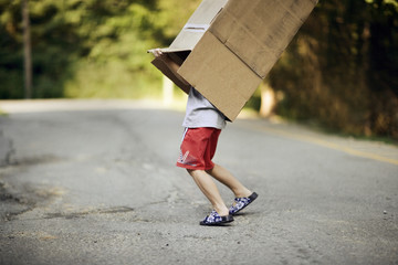 A small boy struggles to remove the box off his body while walking on the road.