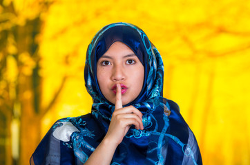 Beautiful young muslim woman wearing blue colored hijab, facing camera posing making silence symbol touching lips with finger, autumn forest background