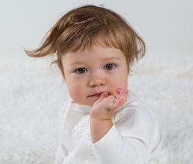 Портрет маленькой девочки, сидящей на кровати