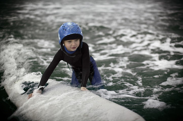 young boy struggles with a surfboard