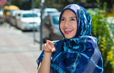 Beautiful young muslim woman wearing blue colored hijab, pointing finger smiling, outdoors urban background
