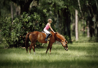 Teenage girl sitting on a horse while it grazes.