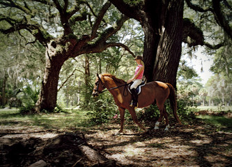 Teenage girl riding a horse through trees.