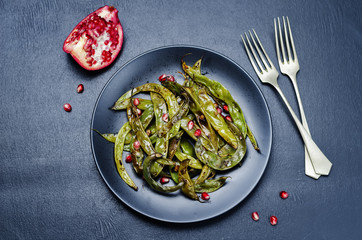 roasted snap green beans with Pomegranate on a black background. toning. selective focus