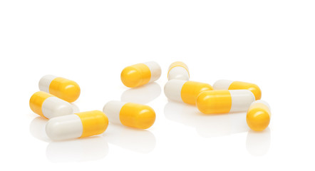 Pile of yellow and white capsules isolated on white background