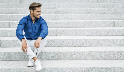 Fashion male model sitting and smiling Wall mural