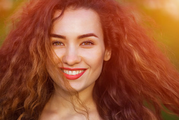 Smiling beautiful, young, skinny, cute girl with curly hair, illuminated by the sun on a beautiful sunset background.