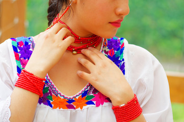 Closeup beautiful hispanic woman wearing traditional andean white blouse with colorful decoration around neck, matching red necklace, bracelet and ear ring
