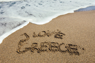 The word I Love Greece written in the sand on beach