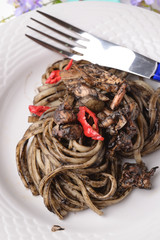 Linguine with squid ink and red pepper flakes on a white background