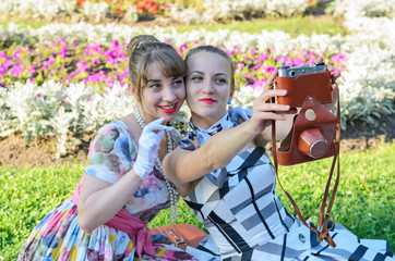 Retro style girls on a picnic taking photos and selfies with an old camera