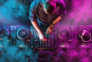 Charismatic disc jockey at the turntable. DJ plays on the best, famous CD players at nightclub...