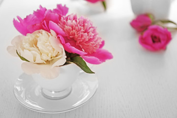 Bouquet of beautiful flowers in a cup on a  table