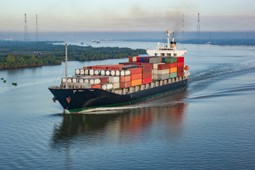 Container ship with many colourful containers in harbour