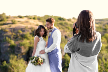 Wedding photographer taking photo of bride and groom