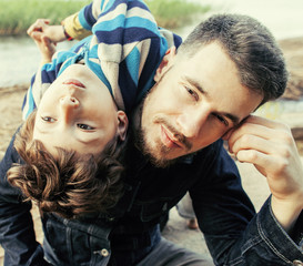 Young father hipster with a beard and his little son on the lake shore. Talking, teaching, having fun happy time. Lifestyle people concept