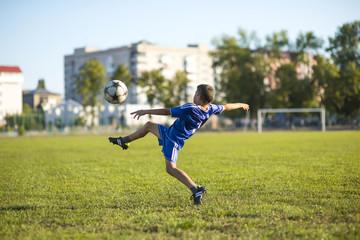 Boy kicking soccer ball on the football field