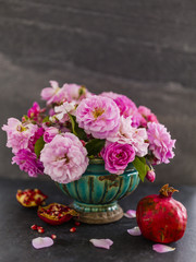 Beautiful pink roses in an old vase and pomegranate fruit. Still life on dark background.