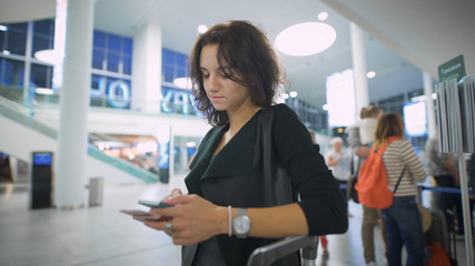 A young lady is thinking about her trip holding her smartphone