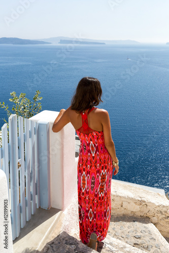 frau im rotem kleid schaut auf das meer in oia santorini. Black Bedroom Furniture Sets. Home Design Ideas