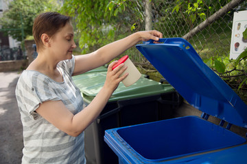 Woman recycling waste in a garbage trash bin. Waste sorting recycling concept.