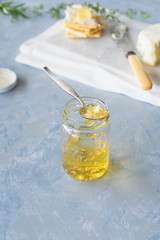Homemade herbs and sweet white wine jelly in small jar. Selective focus.