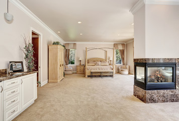 Large master creamy tones bedroom in luxury home.