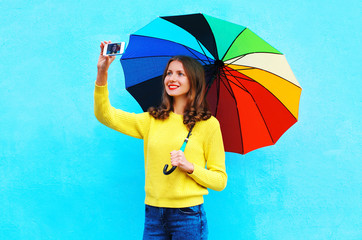 Happy smiling young woman with autumn colorful umbrella taking p