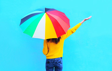 Happy young woman with colorful umbrella raised hands up enjoyin