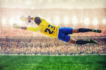 soccer goalkeeper flying to catches the ball in the stadium