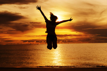 Silhouette happiness woman jump on the beach. She is enjoying travel holidays vacation outdoors sunset.