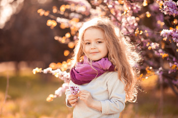 Smiling kid girl 4-5 year old holding flower wearing casual clothes outdoors. Looking at camera. Childhood.