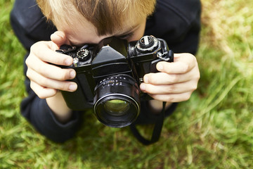 Child blond boy with vintage photo film camera photographing