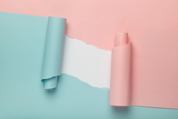 Torn blue and pink colored paper