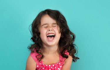 portrait of a happy, positive, smiling, little girl, cyan background