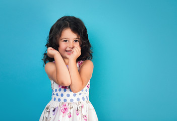 portrait of a happy, positive, smiling, little girl, blue background