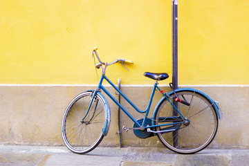 Blue old bicycle standing near bright yellow wall.